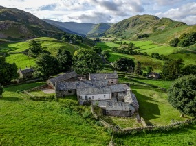 Aerial photograph of stunning remote holiday home in front of Martindale situated in the Lake District, Cumbria bathed in sunshine