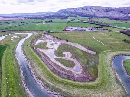 Aerial drone photograph of the newly created wetland area within the bend of the River Gilpin with Whitbarrow Scar on the horizon