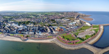 Wide angle panoramic aerial view of Morecambe promenade in early morning bright sunshine